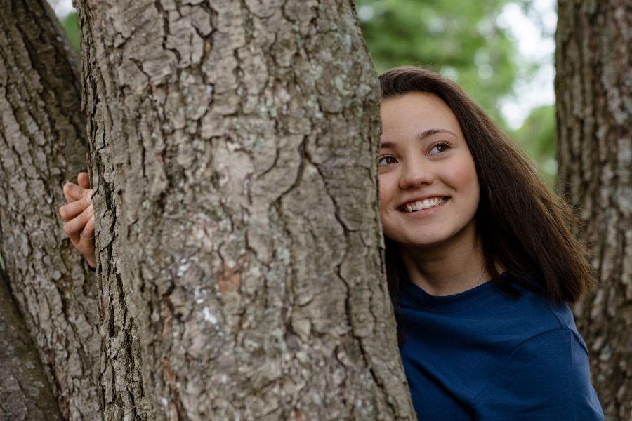 Tyttö katsoo puun takaa