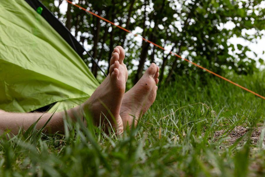 Jalat nurmikolla ja teltta