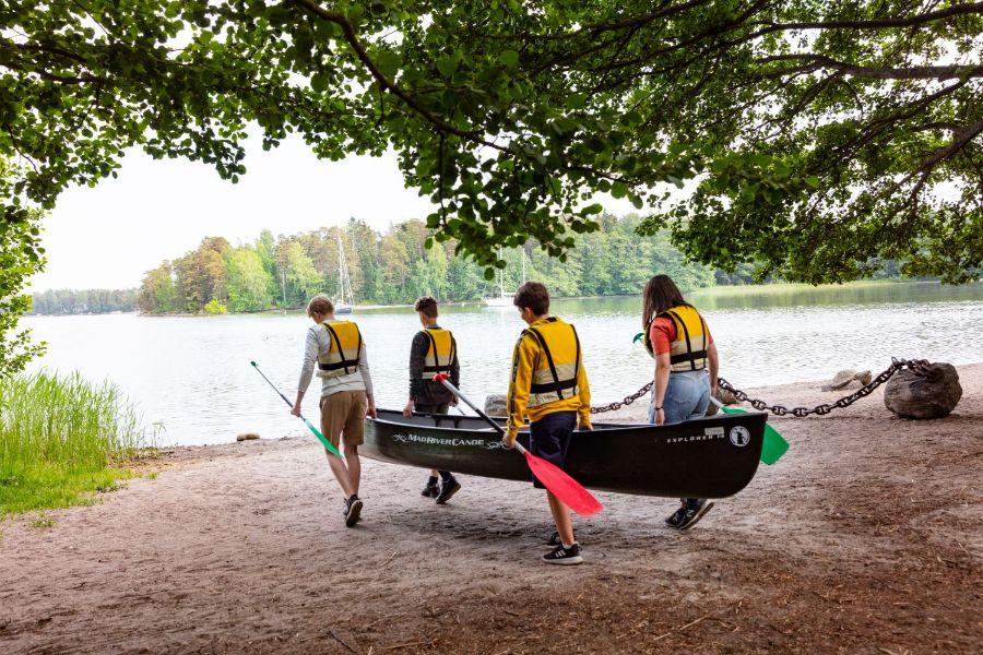 Nuoret kantamassa kanoottia
