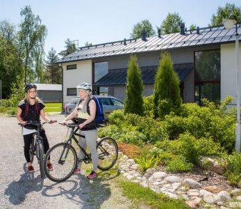 Kaksi nuorta pyöräilee Hyvärilän nuorisokeskuksen alueella.