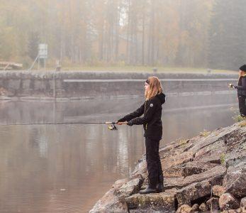 Työttö kalastaa joen rannalla.