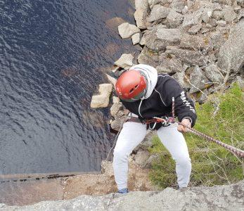 Mies laskeutuu köydellä kalliolta.