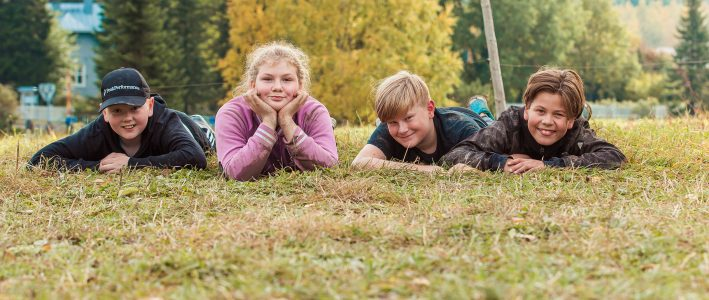 Leirikoululaisia makoilee iloisena nurmikolla.