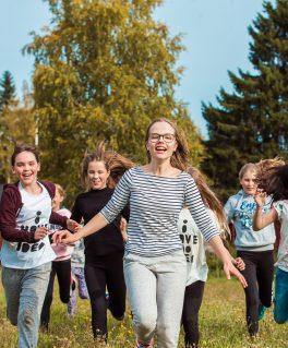Leirikoululaisia juoksee iloisena nurmikolla.