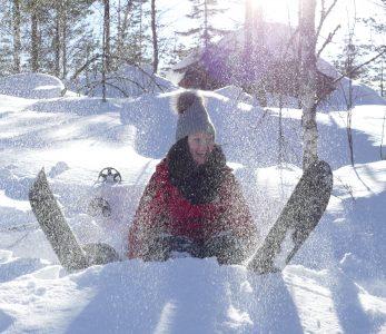 Tyttö istuu paksussa lumikinoksessa iloisena lumisukset jalassaan.