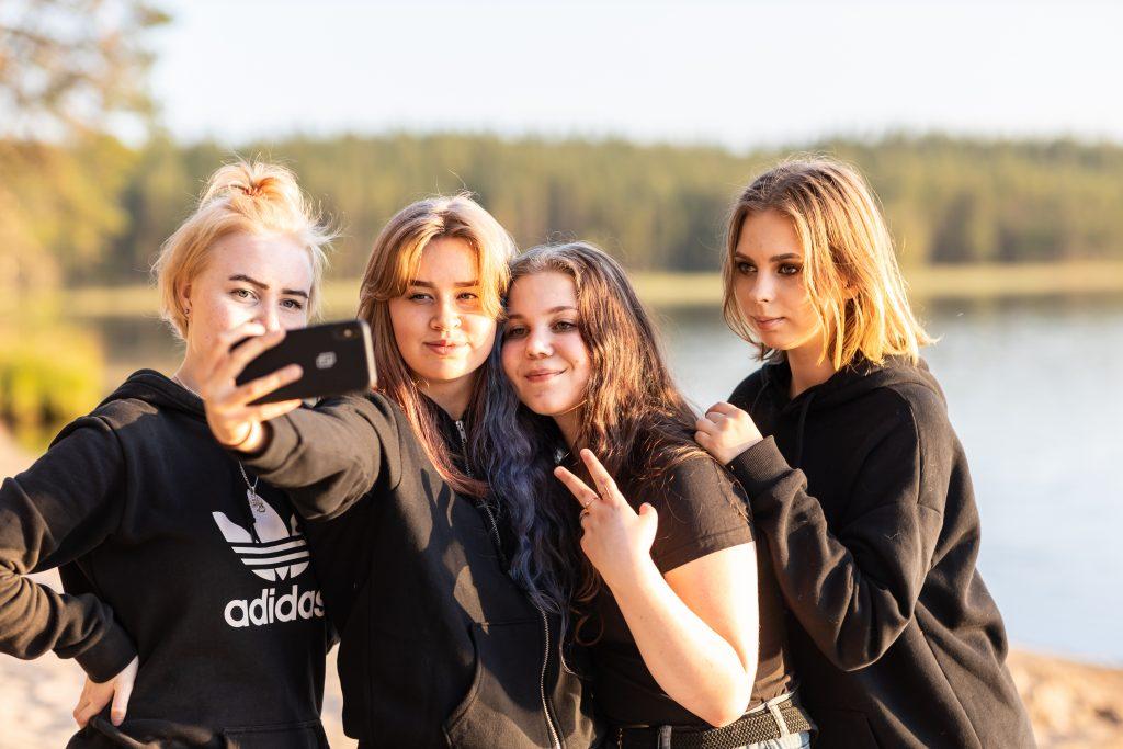 Leirikoululaisia ottamassa selfietä rannalla.