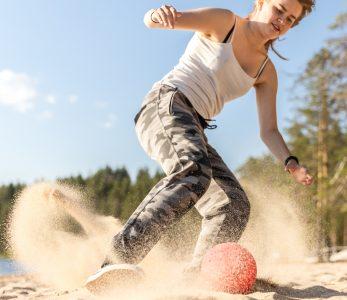 Nainen pelaa rantajalkapalloa hiekalla.