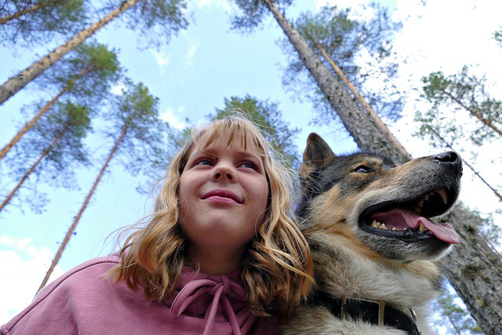 Tyttö ja koira metsässä.