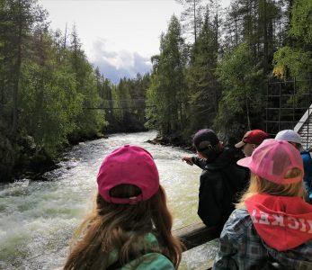 Lapsia katsomassa sillalla, kuinka koskessa virtaa paljon vettä.