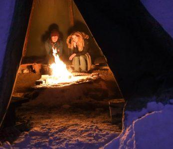 Kaksi nuorta lämmittelee kodassa tulen äärellä.