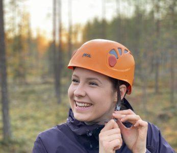 Nainen kiinnittää kypärää metsässä.