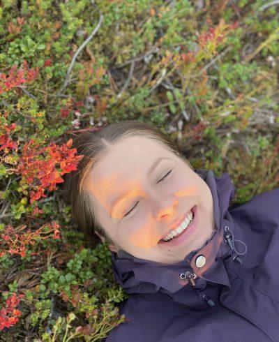 Nainen makaa onnellisena maaruskan seassa.