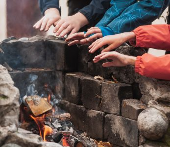 Käsien lämmittelyä leirinuotiolla.