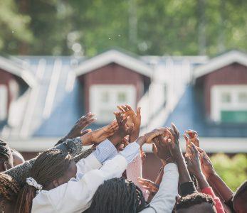 Joukko kansainvälisiä nuoria nostaa käsiä ilmaan.
