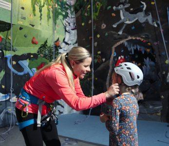 Aikuinen laittaa kypärää lapselle, joka on lähdössä kiipeilemään.