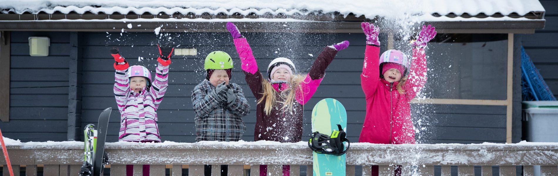 Lapsi heittää lunta ilmaan, taukoa laskettelusta.