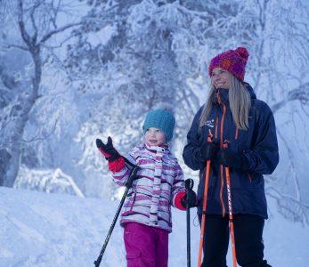 Aikuinen opstaa lasta luminkenkäilyssä Pikku-Syöteellä.