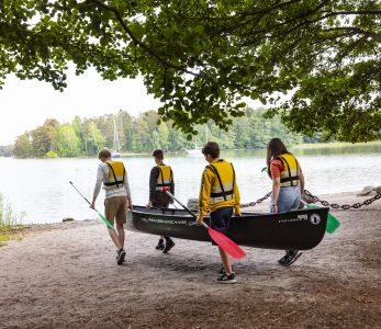 Neljä nuorta kantaa kanoottia rantaan.