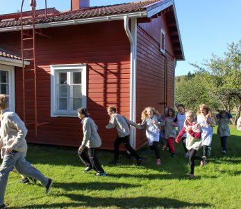 Lapsia juoksemassa vanhan ajan koulupuvuissa.