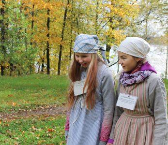 Kaksi tyttöä, joilla päällään vanhanajan koulupuvut.