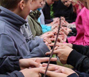 Iso joukko lapsi kannattelee mato-onkea sormenpäillään.
