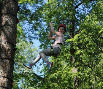 Lapsi laskeutuu köydellä puusta. On kesä.