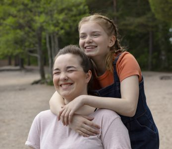 Kaksi nuorta tyttöä halaa kavereina toisiaan.