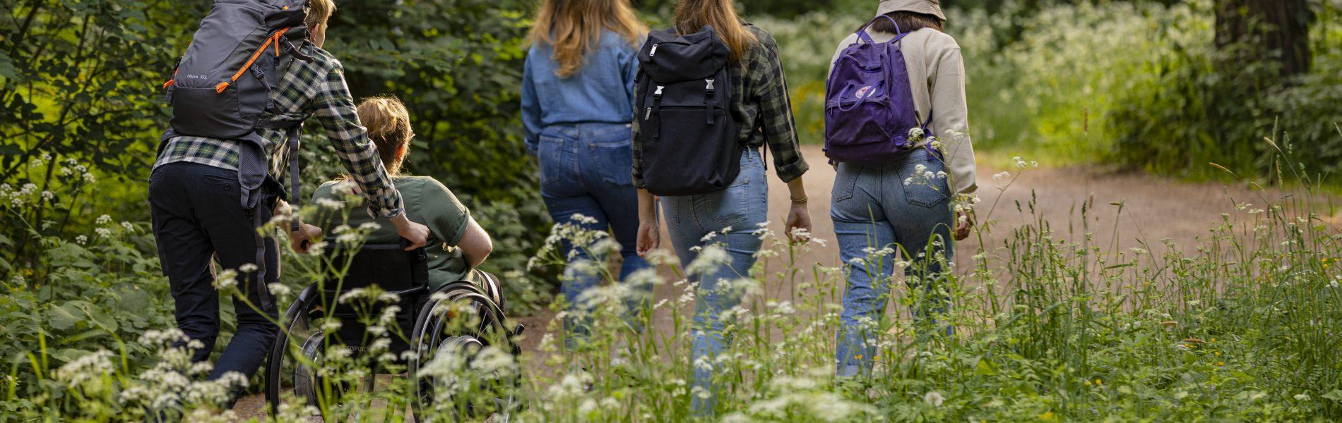 Nuoria kulkee soratietä pitkin retkellä. Kuva otettu takaapäin.