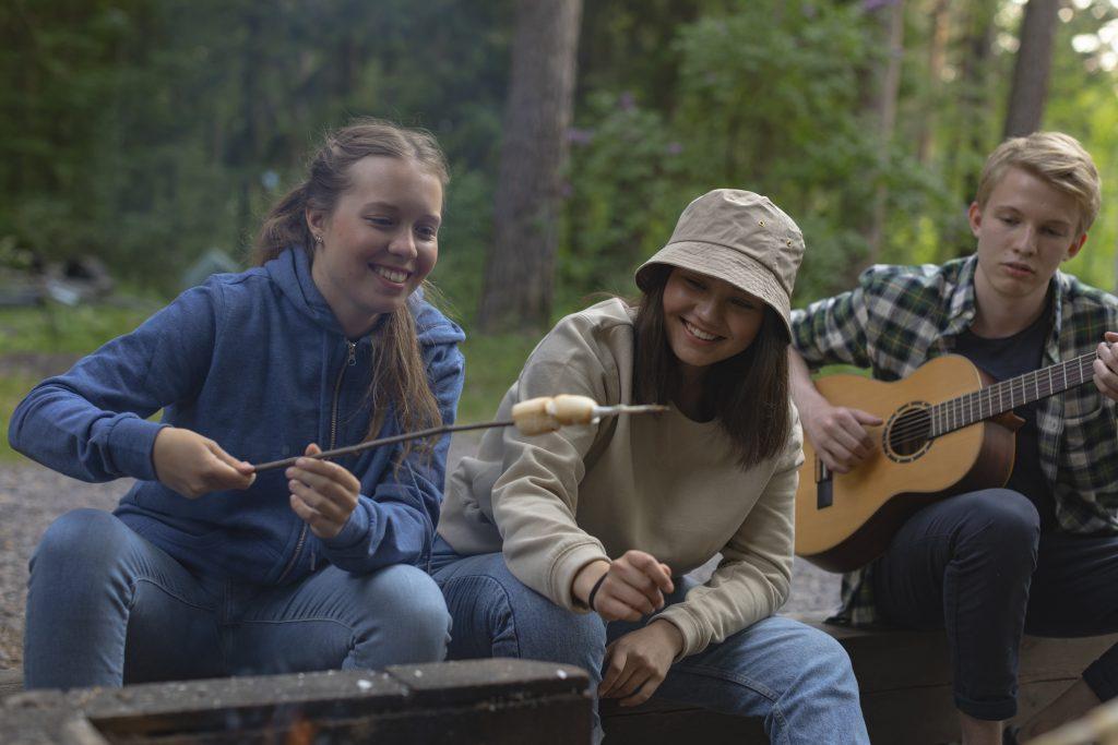 Nuoria nuotiolla, yksi paistaa vaahtokarkki, yksi nauraa ja yksi soittaa kitaraa.