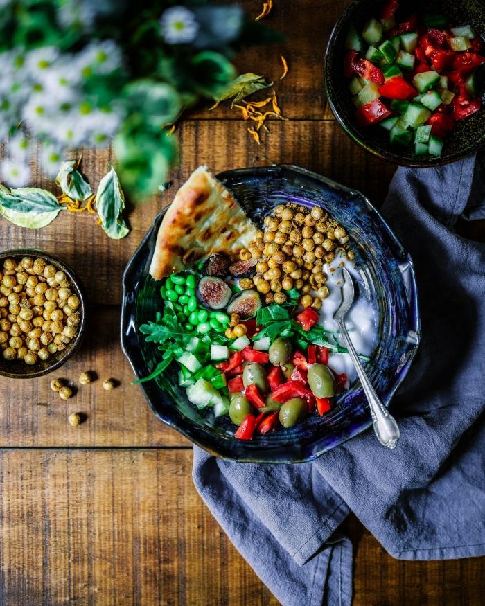 Kasvisruokaa ja koristeita puisella pöydällä.