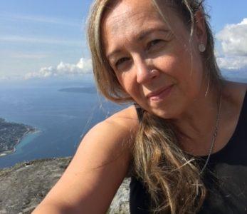 SNK ry:n toiminnanjohtaja Eija Pietilä tunturin huipulla Narvikissa patikointireissulla.