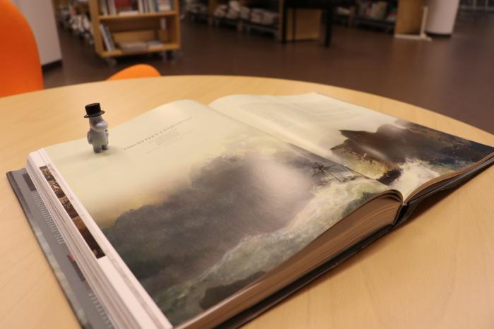 Muumipappa-hahmo avatun kirjan päällä.
