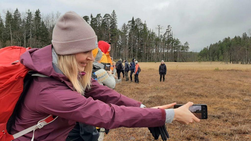 Johanna Sutinen ottamassa selfietä suon läpi kulkevilla pitkospuilla.