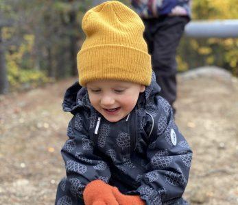 Lapsi kiipeilee iloisena alaköysiradalla.