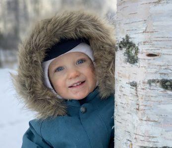 Poika puun takana talvella