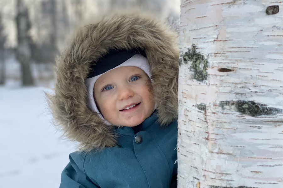 Poika puun takana talvella.