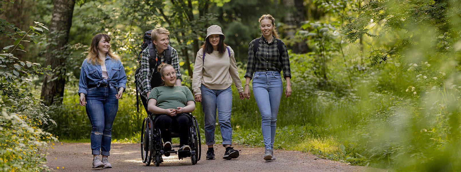 Viisi nuorta lähdössä luontoretkelle, kävelevät soratietä pitkin.