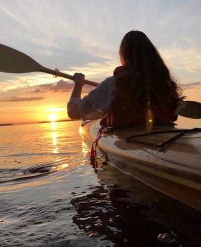 Nainen meloo kajakilla kohti auringonlaskua.
