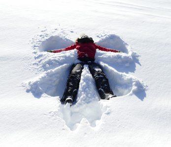 Tyttö tekee lumienkelia paksussa lumihangessa Metsäkartanolla.
