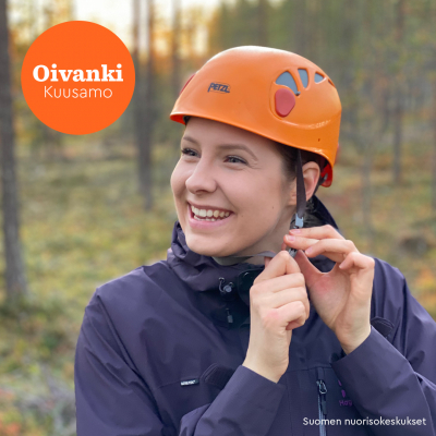 Nainen laittaa iloisena kypärää päähän.