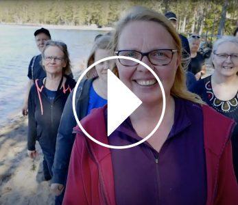 Videon kansikuva, jossa nuorisokeskuksen työntekijöitä kävelee rannalla.