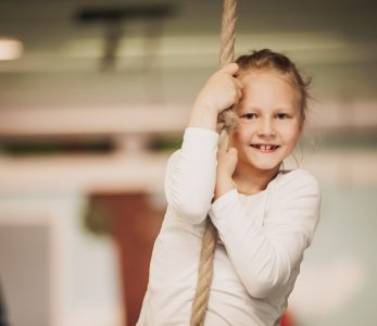 Tyttö kiipeilee köydellä.