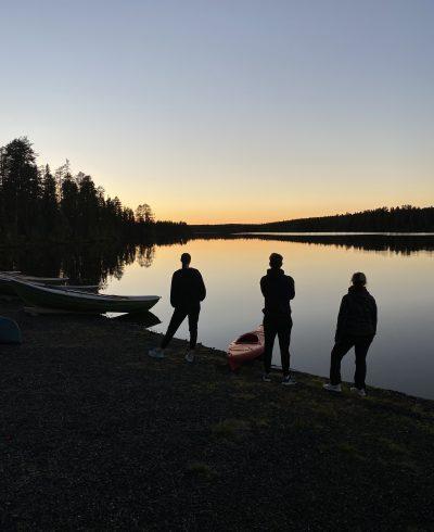 Silhuettikuvassa ihmisiä ja veneitä rannalla ilta-auringossa.