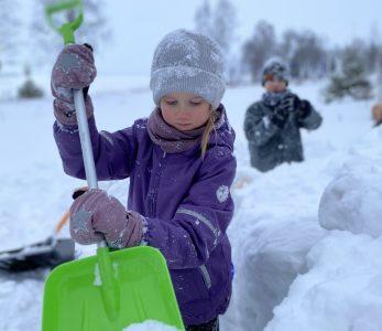 Lapsi lapioimassa lunta lumilinnaa varten. Taustalla toinen lapsi touhuissa mukana.
