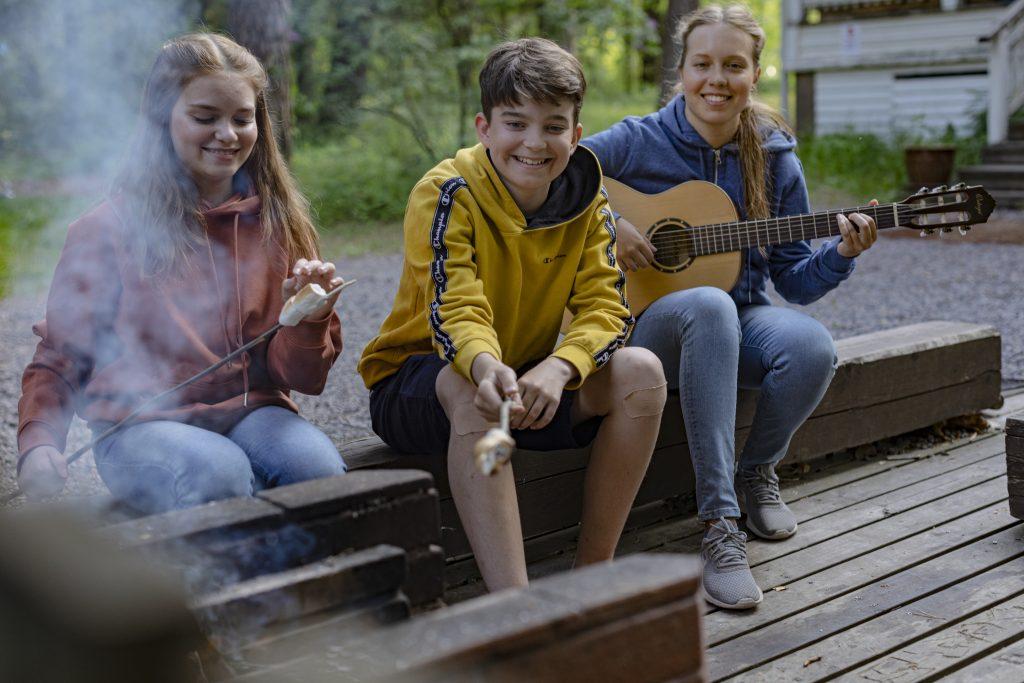 Kolme nuorta rippileirillä iltanuotiolla. Kaksi paistaa vaahtokarkkeja tikuilla, kolmas soittaa kitaraa.
