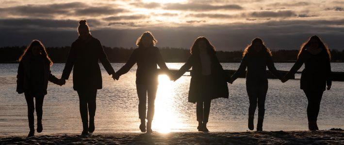 Silhuettikuva rannalta, jossa on toisiaan kädestä kiinni pitäviä nuoria.